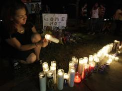 Esmeralda Carbajal lights candles at a growing memorial across the street from the Century 16 movie theater in Aurora, Colo.