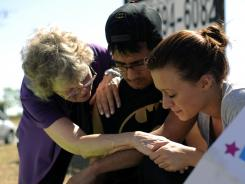 Pastor Mary Lu Saddoris, left, comforts Isaac Pacheco and Courtney McGregor on Saturday at a memorial in Aurora, Colo.