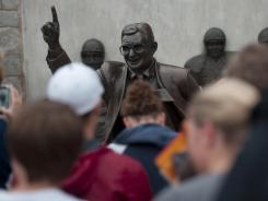 Visitors pose for photographs Friday with the statue of former Penn State football coach Joe Paterno outside Beaver Stadium.