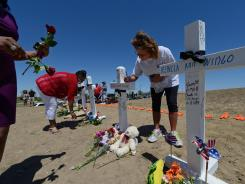 Women place flowers and write messages on white wood crosses Sunday with the names of each victim killed during the mass shooting in Aurora, Colo.
