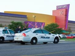 "Police cars in front of the Century 16 theater in Aurora, Colo., where a gunman opened fire during the opening of the new Batman movie, ""The Dark Knight Rises."""