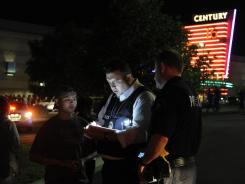 An Aurora Police Department detective takes a witness statement following a shooting on July 20.