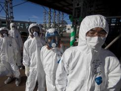 Workers in protective suits wait to enter the crippled Fukushima Dai-ichi nuclear power station in Okuma, Japan, on Nov. 12.