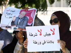 "Libyan protesters hold the portrait of Nabil al-Alam and a sign that reads in Arabic, ""No army, no police , our country is in trouble,"" during a sit-in calling for his release."