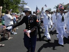 A Marine in uniform hands out flags in front of a group of sailors as they march in the gay pride parade Saturday in San Diego.