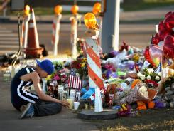 A young man sits on the sidewalk Sunday next to a makeshift memorial to the victims of the shooting in Aurora, Colo.