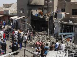 People inspect the scene of a bomb attack in Madain, about 15 miles southeast of Baghdad on Monday.