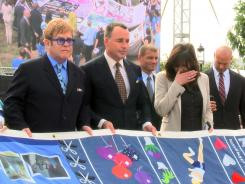 Musician Elton John, left, and his partner, David Furnish, hold the AIDS Memorial Quilt on Monday in Washington.