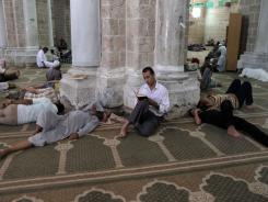 Palestinians rest as a man reads the Quran in al-Omari mosque in Gaza City on Friday, the first day of the Muslim fasting month of Ramadan.