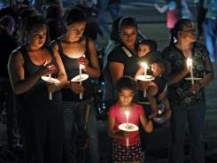 Sunday vigil: Mourning the victims across the street from the movie theater in Aurora, Colo.