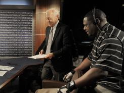Stage Manager Troy Thornes, right, assists Bob Schieffer, CBS News' chief Washington correspondent, as the veteran reporter prepares to host 'Face the Nation' from the network's Washington studio on Sunday.