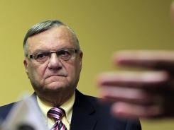 Maricopa County Sheriff Joe Arpaio listens to one of his attorneys during a news conference in Phoenix on April 3.