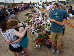 Shooting victim Gordon Cowden's family members embrace Monday at a makeshift memorial across the street from the movie theater in Aurora, Colo.