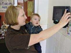 Megan Fleegel and her son, Britton Bloch, demonstrate the fingerprint security system at Playhouse Child Care Center in Sartell, Minn.