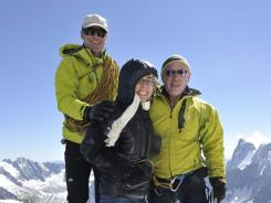 Former U.S. congresswoman Gabrielle Giffords, center, who is recovering from injuries in a mass shooting last year, and her husband Mark Kelly, right, accompanied by mountain guide Vincent Lameyre, stand on a ridge of the Aiguille du Midi, above Chamonix, France, in the French Alps.
