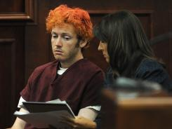 Public Defender Tamara Brady, right, shows James Holmes documents in Arapahoe County District Court on Monday.