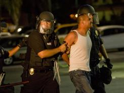 A man is arrested by police in Anaheim, Calif., Tuesday night as police attempt to disperse the unruly crowd.