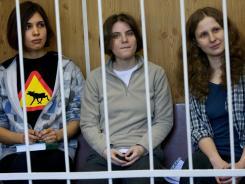 From left, Nadezhda Tolokonnikova, Maria Alekhina and Yekaterina Samutsevich sit behind bars at a court room in Moscow on Monday.
