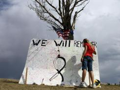 A girl signs a message board at a memorial across the street from the Century 16 movie theater in Aurora, Colo.