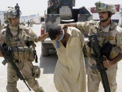 Iraqi army soldiers bring in a blindfolded and handcuffed suspected al-Qaeda member to detention centers in an Iraqi army base in Baghdad on July 25.