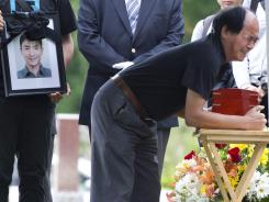 Daran Lin hugs the urn bearing the remains of his son, Jun Lin, during funeral services Thursday in Montreal.