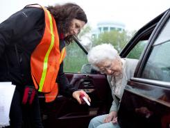 Catherine Sullivan, who teaches occupational therapy, helps Geraldine Thompson, 86, during a CarFit clinic in St. Paul in April.