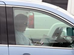 A driver types on her cellphone while driving near Pacific Coast Highway in Long Beach, Calif..
