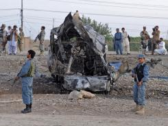 Afghan soldiers stand guard near the site of a suicide car bomb attack in Kandahar, Afghanistan, on July 2.