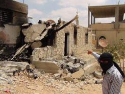 A masked man points to a damaged building in the town of Qara outside Damascus, Syria, on Thursday.