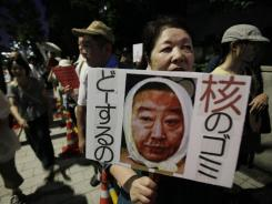 A woman holds a poster with an image of Japanese Prime Minister Yoshihiko Noda during an anti-nuclear protest outside Noda's official residence in Tokyo last Friday.