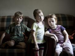 Tone, Mara and Liza watch TV in the Luci family home in Tirana, Albania. The Luci family has been in blood feud since 1997, when a family member killed three people.