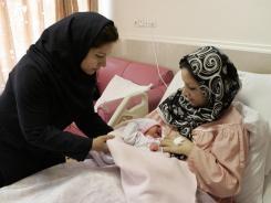 Iranian nurse Zahra Akbarzadeh, left, gives one-day-old baby girl Setayesh to her mother, Tayyebeh Sadat Bidak at the Mehr hospital in Tehran on Sunday.