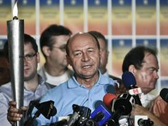 Suspended Romanian President Traian Basescu holds a torch while speaking at the end of the referendum in Bucharest, Romania, on Sunday.