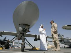 An Emarati visitor asks a U.S. military representative questions as they stand next to an MQ-1 Predator spy plane.