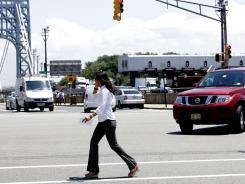 A pedestrian talks on a cellphone while crossing an intersection near the George Washington Bridge in Fort Lee, N.J.