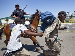 Protesters run as a police officer on horseback gallops towards them Sunday in Anaheim, Calif., where residents along with Occupy members gathered to protest two fatal police shootings.