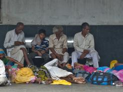 Indian passengers sleep and rest on the platform as they wait for their train at a railway station following an overnight regionwide power outtage in New Delhi.