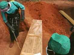 A worker from St. Mary's Lacor Hospital in Gulu disinfects the coffin of an Ebola victim in northern Uganda on Nov. 1, 2000.