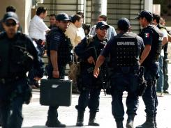 Members of the anti-explosive unit of the Mexican Federal Police are seen at a branch of the El Norte newspaper on July 10 in Monterrey, Nuevo Leon State, Mexico.