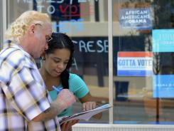Alaysha Claiborne, 18, helps Leo Wright fill out a voter registration form while volunteering for the Obama campaign in York, Pa., on Thursday.