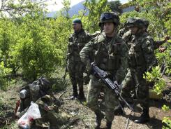 Soldiers patrol near coca fields July 18. The White House says Colombia's cocaine production fell 25% in 2011.