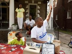 From left, Dwayne Durant, 10, and Joshua Smith, 9. hold a lemonade and popcorn sale to benefit Detroit at Smith's home, as his mother, Rhonda Smith, 43, father Flynn Smith, 43, and brother Nathanie Smith, 4, look on.