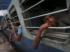 A young Indian boy watches from a window of a stalled train in New Delhi, India, on Tuesday.