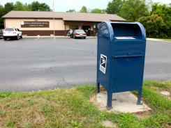 A mailbox sits outside a U.S. Post Office in Lawrence, Mich.