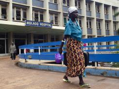 A woman walks by Mulago Hospital on Tuesday in Kampala, Uganada, where one person who contracted the deadly Ebola virus died.