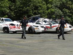 Sheriff officers walk past crushed cruisers at the Orleans County Sheriff's Department in Newport, Vt., Thursday.
