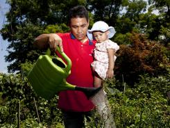 Burmese refugee Maung Thesein and 1-year-old daughter Khine Nein Thazin, who have been in the U.S. for less than a month, water plants at Drew Gardens in the Bronx.