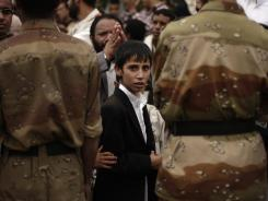 A Yemeni boy and other protestors are blocked by soldiers during a demonstration demanding the removal of former President Ali Abdullah Saleh's relatives and allies from key military and security positions, Aug. 3.