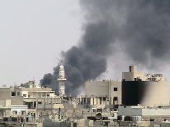 Pillars of smoke as a result of shelling by Syrian government forces darken the sky near al-Zafaran mosque in Homs.