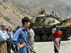 Residents stand near Turkish armored vehicles outside a military outpost where Kurdish rebels attacked and killed 6 soldiers and 2 village guards Sunday.